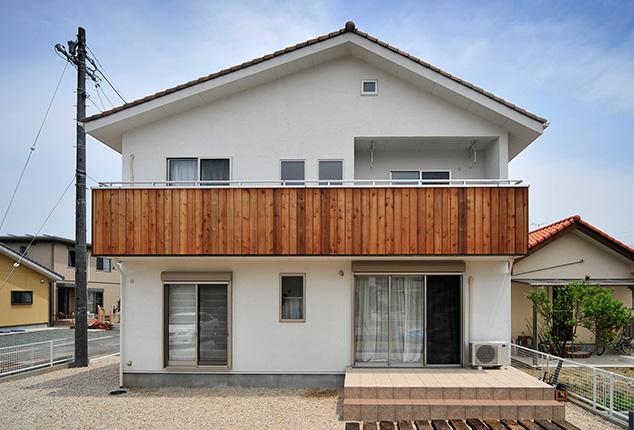 白い外壁と広い駐車スペースの家