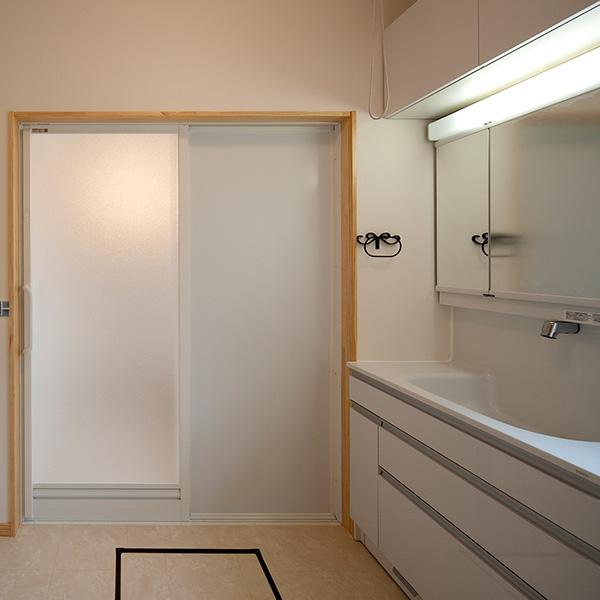 清潔感がいっぱいの洗面スペースです。洗面台は大きく、鏡も収納もあわせて大きな物を設置しました。扉の先は浴室になっています。