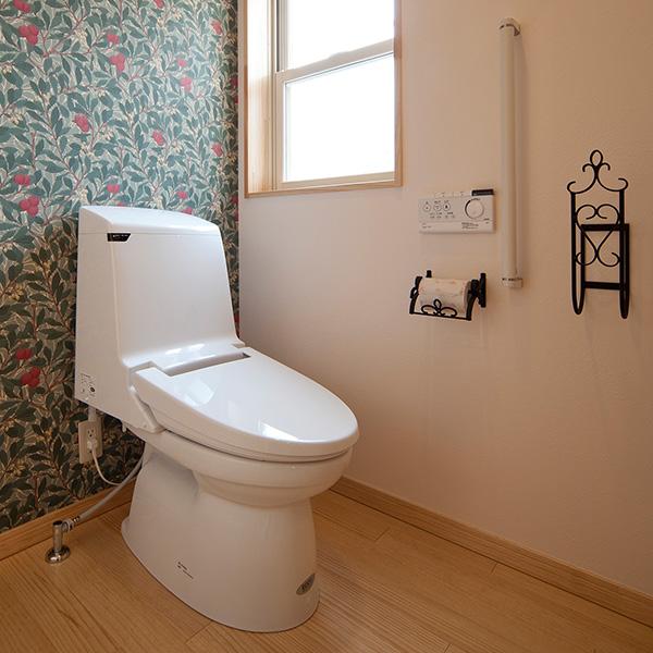 トイレスペースです。色鮮やかな壁紙が特徴的です。木材の床や、ペーパーホルダーなどこだわりがたっぷりあります。