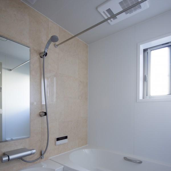 浴室は優しい色合いで仕上げ物干し用のランドリーパイプをつけました。