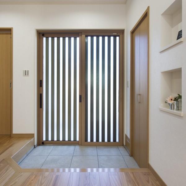 木目柄の玄関引き戸が素材感溢れる温かみのある玄関を演出します。