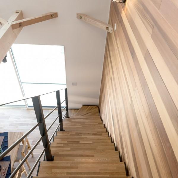 壁に貼ったレッドシダーの無垢材とブラックの鉄骨のストリップ階段が大きな吹抜空間にぴったりです。